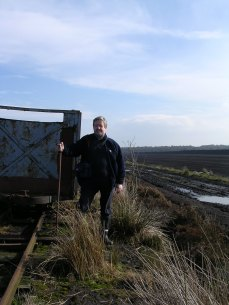 Professor Keith Barber at Bolton Fell Moss in 2004 next to train line and carraige. Sea of brown milled peat visible in background.